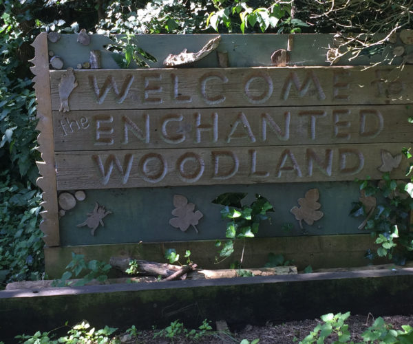 A wooden sign that says welcome to the Enchanted Woodland sign
