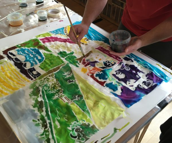 Hand painting landscape design onto silk